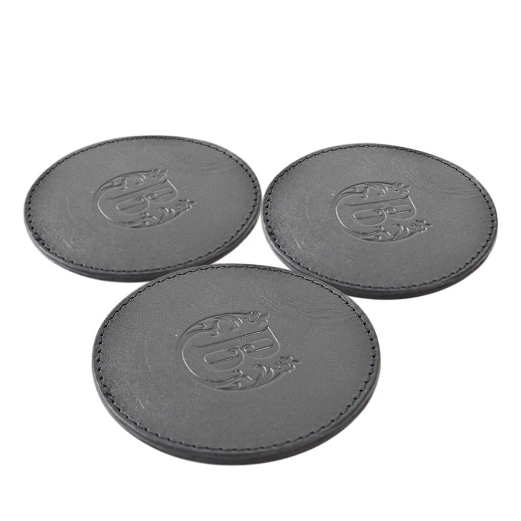 Posavasos fabricados en piel genuina de origen bovino, de 9 cm. de diámetro y 3 mm. de grosor aprox. Color negro. Incluye logo en bajo relieve. Presentado en bolsa individual.