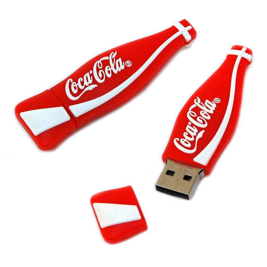 Memoria USB con forma de botella Coca-Cola, fabricada en rubber. De medidas 70x20x11mm aprox. Capacidad 4 GB. Sin información grabada en su interior. Incluye personalización de logo Coca-Cola a un color en dos posiciones. Presentado en caja blanca individual.
